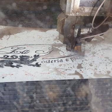 Taglio insegna in acciaio INOX pellicolato